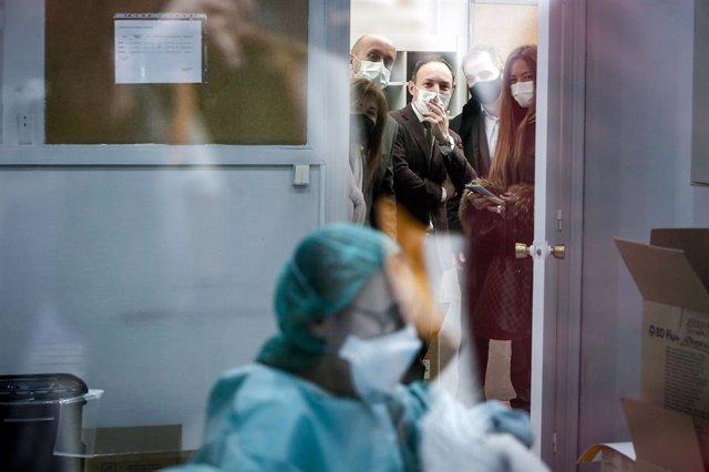 El cap de Govern d'Andorra, amb els ministres de Salut i de Justícia i Interior observant una professional preparant dosi al centre d'administració de vacunes