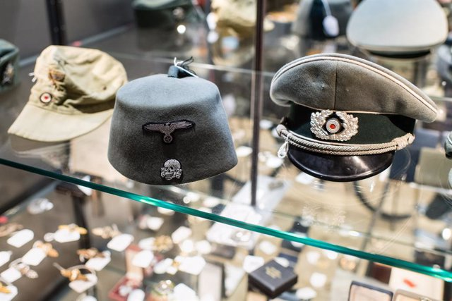 Archivo - 20 November 2019, Bavaria, Grasbrunn: A tropical army field cap, a fez for the field uniform of the Muslim legionnaires of the Waffen-SS and an umbrella cap for officers of the infantry are seen on display at the Hermann Historica auction house