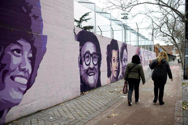 Archivo - Una mujer pasa por el mural feminista en el polideportivo municipal de la Concepción en el distrito de Ciudad Lineal
