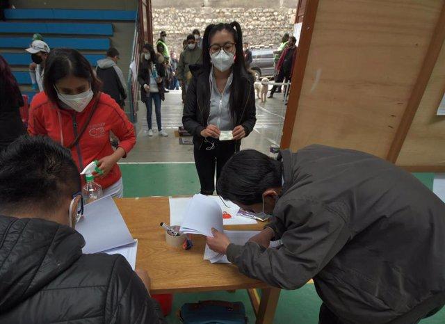 Archivo - Un grupo de personas acude a su colegio electoral en La Paz, durante las elecciones generales de Bolivia, celebradas este domingo