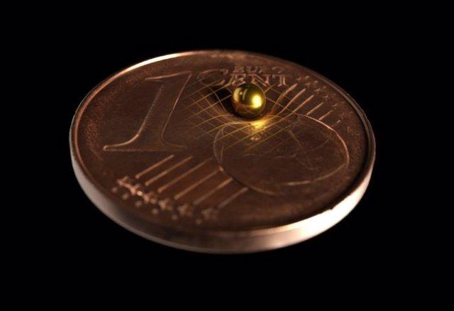 La bola de oro utilizada en comparación de tamaño con una moneda de 1 centavo. Según la teoría de la relatividad general de Einstein, toda masa dobla el espacio-tiempo