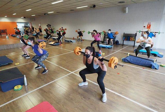Un grupo de personas realiza deporte en la sala de un gimnasio.
