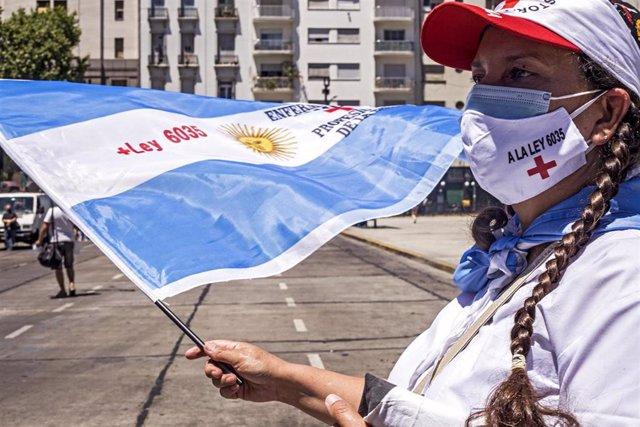 Archivo - Imagen de archivo de una mujer con mascarilla y la bandera de Argentina en una protesta para exigir mejores condiciones laborales para los trabajadores médicos.
