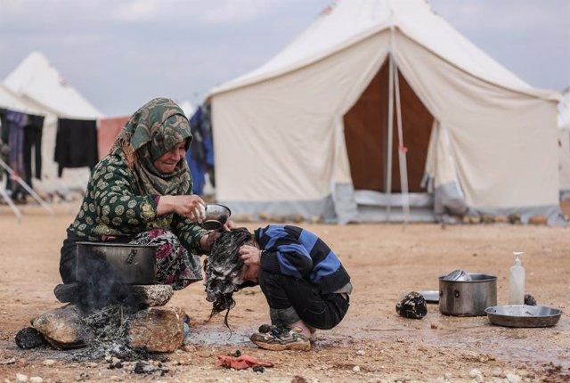 Archivo - Una mujer y un niño en un campamento de desplazados en la provincia de Idlib, en el noroeste de Siria