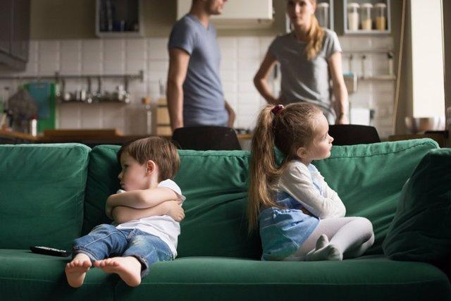 Hermanos peleados sentados en el sofá.