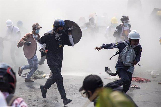 Un grupo de manifestantes se dispersa después de que la Policía lance gas lacrimógeno durante una manifestación contra el golpe militar en Rangún, la ciudad más poblada de Birmania.
