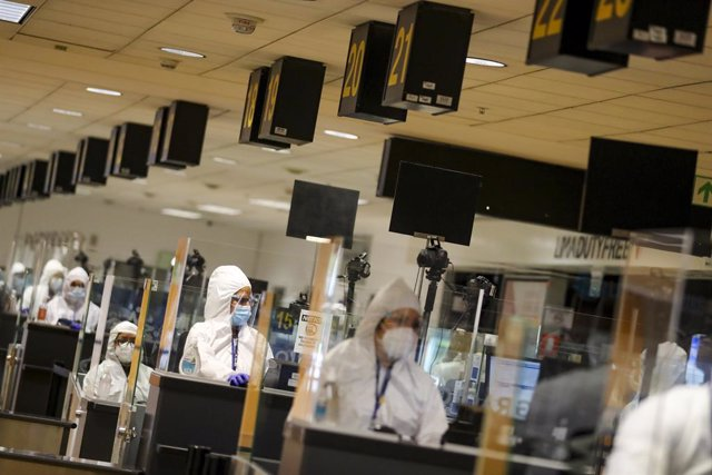 Archivo - HANDOUT - 05 October 2020, Peru, Lima: Airport employees in protective suits operate at the passport control desks of the Jorge Chavez airport after international flights resumed following a long shutdown due to the coronavirus pandemic. Photo: