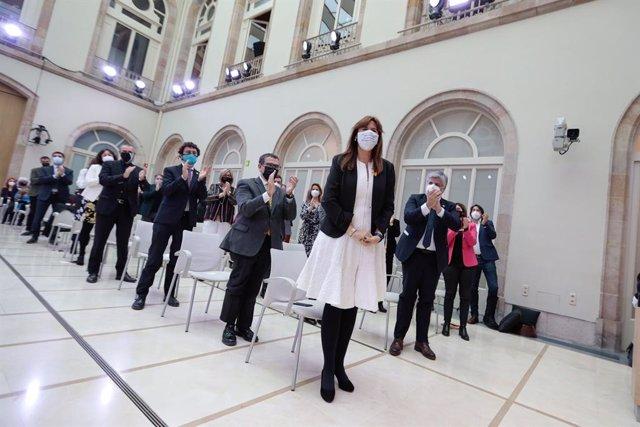 Pla general dels diputats de JxCat dempeus aplaudint Laura Borràs després de ser elegida presidenta del Parlament el 12 de març del 2021