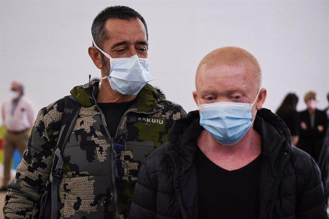 El doctor Pedro Cavadas, a la izquierda, con el joven albino guineano al que ha operado de cáncer facial