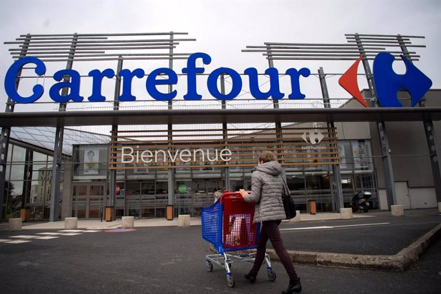 Archivo - 13 January 2021, France, Saint-Herblain: A woman enters a French retail supermarket Carrefour. A visitor enters a supermarket of the French retail group Carrefour. Europe's largest retail group Carrefour has been targeted by its Canadian competi
