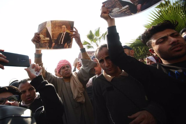 Archivo - 26 February 2020, Egypt, Cairo: Supporters of Egyptian former President Hosni Mubarak grieve outside the cemetery in Cairo's Heliopolis suburb where Mubarak has been buried after his military funeral. Mubarak, who ruled Egypt for three decades,