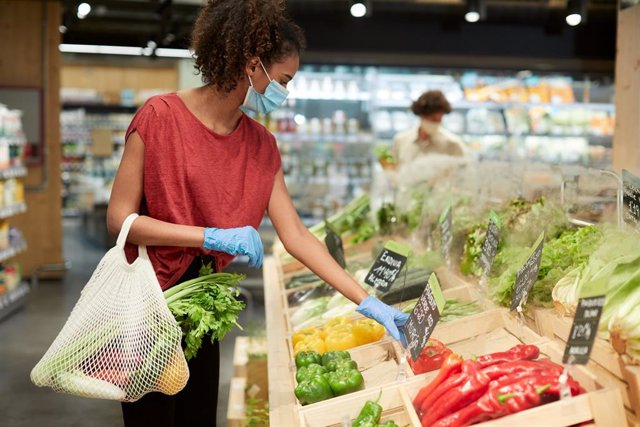 Mujer comprando verduras con mascarilla y guantes en un supermercado.