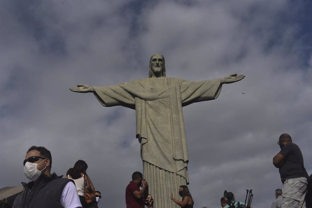 Archivo - Personas con mascarilla por el coronavirus junto al Cristo del Corcovado de Río de Janeiro