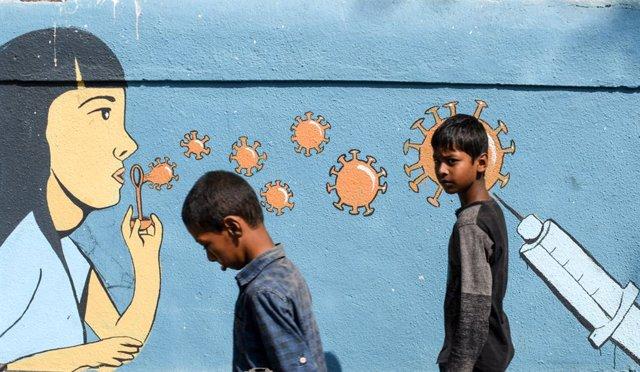 05 March 2021, India, Mumbai: Boys walk past a mural raising awareness about coronavirus in Mumbai. Photo: Ashish Vaishnav/SOPA Images via ZUMA Wire/dpa