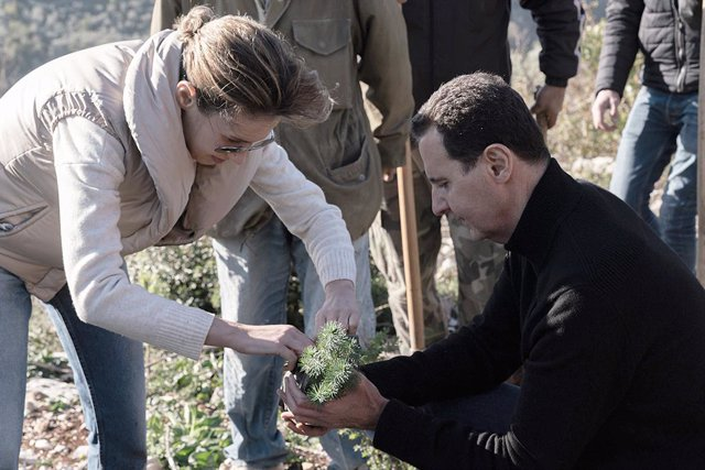 Archivo - FILED - 30 December 2020, Syria, Draykish: A picture provided by the Syrian Arab News Agency (SANA) on 30 December 2020 shows Syrian President Bashar Al-Assad (R) and his wife Asma Al-Assad participating with more than 300 Syrian students in the