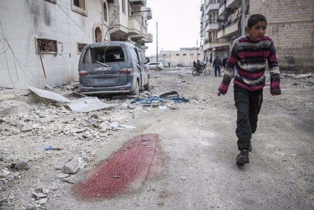 Archivo - Un niño en una localidad de Idlib (Siria) tras varios bombardeos contra un hospital achacados a Rusia