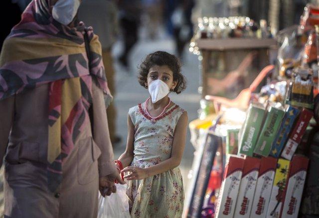 Archivo - Una niña con mascarilla por el coronavirus en Irán