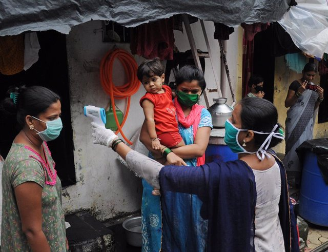 Archivo - Una trabajadora del sistema de Salud toma la temperatura de un grupo de personas de un asentamiento irregular en el suburbio de Mankhurd, en el este de Bombay, India.