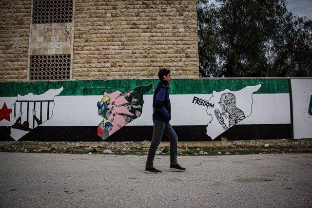 Un joven pasea ante un ural en Idlib