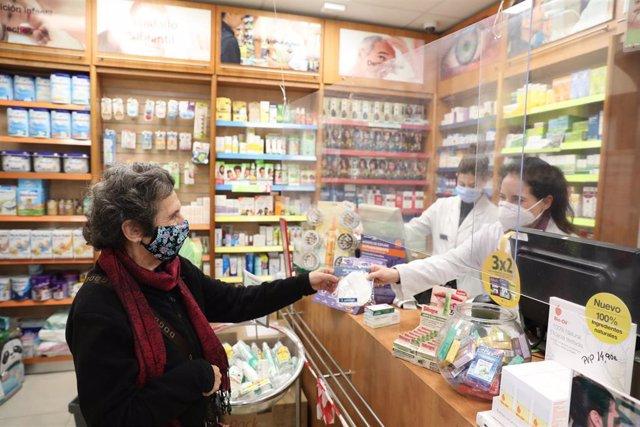 Archivo - Una anciana recoge una mascarilla FFP2 en la farmacia situada en la C/Tucán (Carabanchel), en Madrid (España), a 4 de febrero de 2021. Los mayores de 65 años de la Comunidad de Madrid pueden recoger a partir de hoy la primera de las dos mascaril