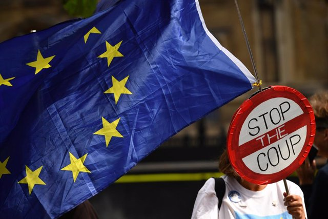 Archivo - 04 September 2019, England, London: A pro-European demonstrator waves an EU flag and a sign in front of the parliament building in Westminster. Photo: Dominic Lipinski/PA Wire/dpa