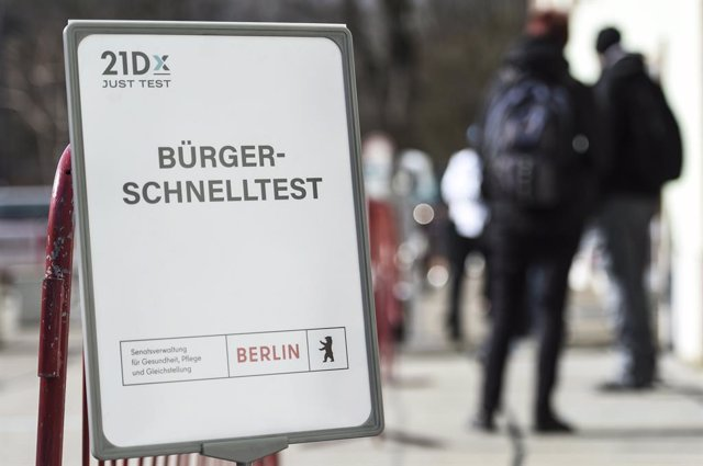 "09 March 2021, Berlin: People queue in front of the coronavirus (COVID-19) rapid test centre on Lehrter Strasse behind a sign reading ""Citizens' Rapid Test"". Photo: Kira Hofmann/dpa-Zentralbild/dpa"