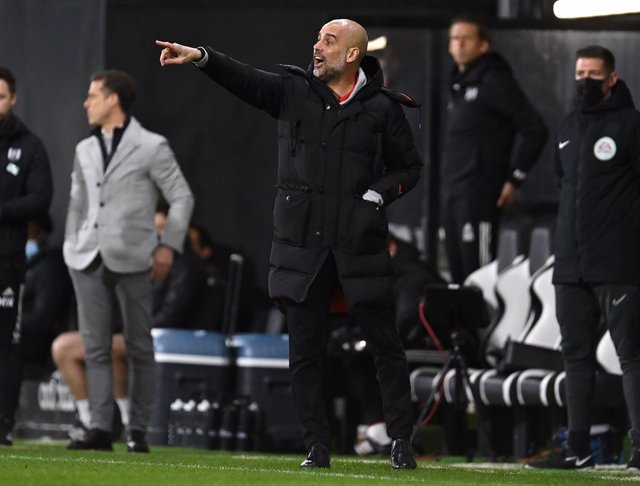13 March 2021, United Kingdom, London: Manchester City coach Pep Guardiola instructs his players during the English Premier League soccer match between Fulham and Manchester City at Craven Cottage. Photo: Justin Setterfield/PA Wire/dpa