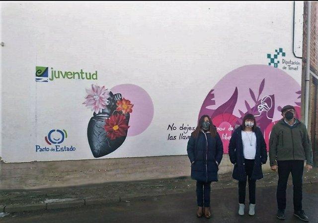 La diputada delegada de Igualdad de la DPT, Susana Traver, visita el mural pintado en una de las paredes del colegio público de Villarquemado acompañada por al alcalde de la localidad, Federico Serrano