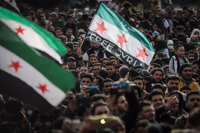 15 March 2021, Syria, Idlib City: People wave flags of the Syrian opposition during a mass demonstration held to mark the tenth anniversary of the start of the Syrian civil war. Photo: Anas Alkharboutli/dpa