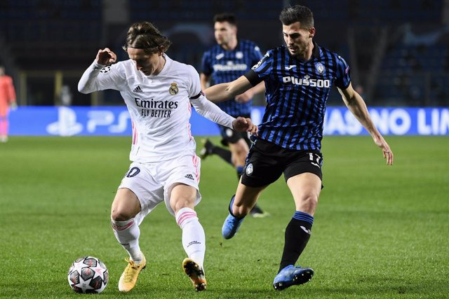 24 February 2021, Italy, Bergamo: Real Madrid's Luka Modric (L) and Atalanta's Cristian Romero battle for the ball during the UEFA Champions League round of 16 first leg soccer match between Real Madrid and Atalanta BC at Gewiss Stadium. Photo: Marco Alpo