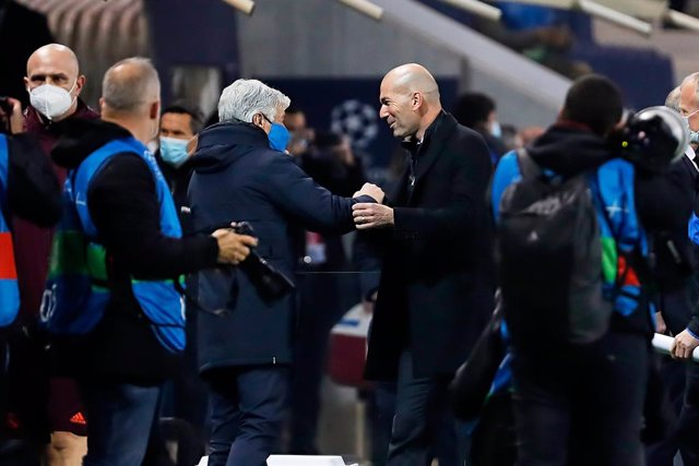 24 February 2021, Italy, Bergamo: Real Madrid head coach Zinedine Zidane (R) and Atalanta head coach Gian Piero Gasperini greet each other during the UEFAChampions League round of 16 first leg soccer match between Real Madrid and Atalanta BC at Gewiss St