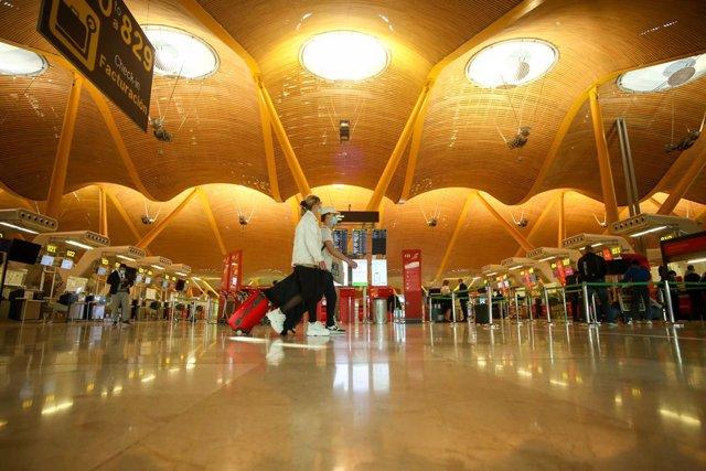 Dos personas caminan con su equipaje en la Terminal T4 del Aeropuerto Adolfo Suárez Madrid-Barajas, en Madrid (España), a 15 de marzo de 2021. El Gobierno ha prorrogado hasta el próximo 30 de marzo la limitación de los vuelos directos y buques de pasaje e