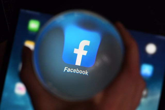 Archivo - FILED - 10 June 2020, Baden-Wuerttemberg, Karlsruhe: A person looks at the Facebook app through a glass ball on a tablet. Facebook's cybersecurity team has identified a state-backed hacking group in Vietnam by tracking them down to an IT firm ba
