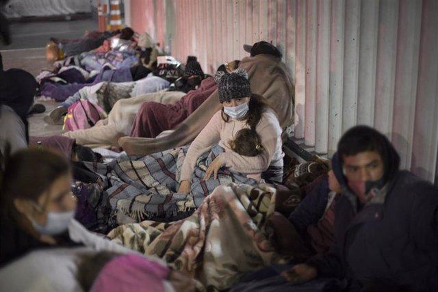 Migrantes esperando junto al paso fronterizo de El Chaparral, en México