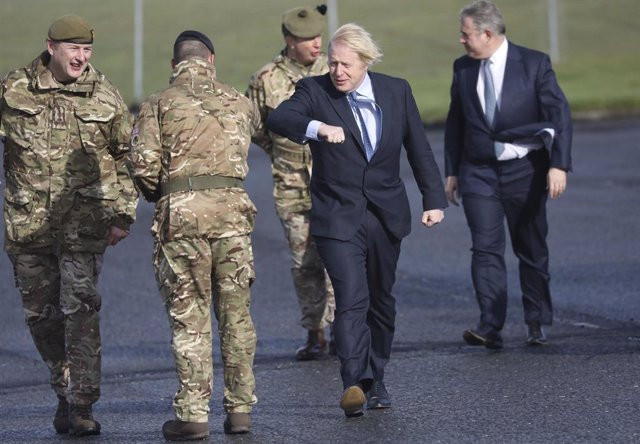 12 March 2021, United Kingdom, Belfast: UKPrime Minister Boris Johnson greets troops alongside Northern Ireland Secretary Brandon Lewis (R) and Brigadier Chris Davies, Commander 38 Irish Brigade (L), during a visit to Joint Helicopter Command Flying Stat
