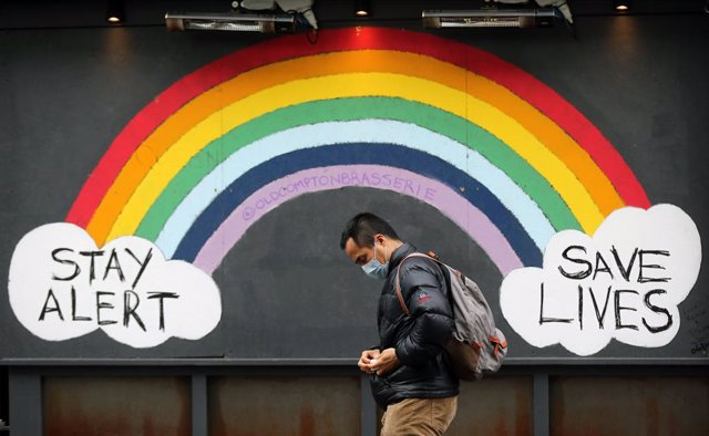 """17 February 2021, United Kingdom, London: A man wearing a mask walks past a graffiti with the message """"·Stay alert, save lives""""  in Soho district as the coronavirus lockdown continues in the city. Photo: Tayfun Salci/ZUMA Wire/dpa"""