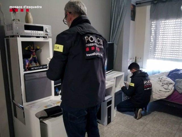 Dos agents durant l'escorcoll en un dels habitatges del detingut.