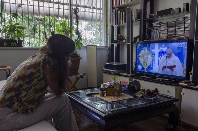 Una mujer asiste a una misa televisada del papa Francisco en su casa.