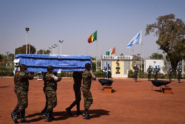 Archivo - 19 January 2021, Mali, Bamako: Soldiers carry the coffin of one of the four Ivorian peacekeepers who died following an attack on January 13, 2021, during the commemorative ceremony held at the headquarters of United Nations Integrated Multidimen
