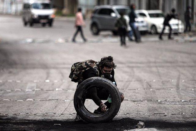 Un manifestante prepara una barricada en Líbano durante las protestas contra el Gobierno por la crisis económica