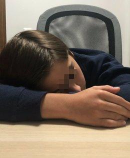 Imagen de un menor descansando sobre la mesa