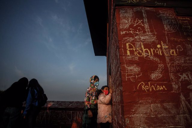 FILED - 16 February 2021, Nepal, Kathmandu: Children write with chalks on the wall of Saraswati temple during Basant Panchami festival, on this day people especially children go to the temple for their first writing and reading lessons in the belief that