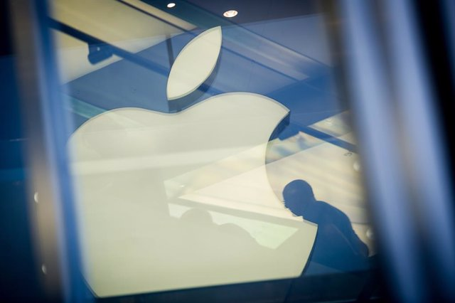 """Archivo - FILED - 01 November 2013, Hamburg: A man sits next to the Apple logo which is reflected on a facade of the Apple store in Hamburg. Today, Monday, the Technology company Apple announced that the """"App Store"""" currently supports 250,000 jobs in Germ"""