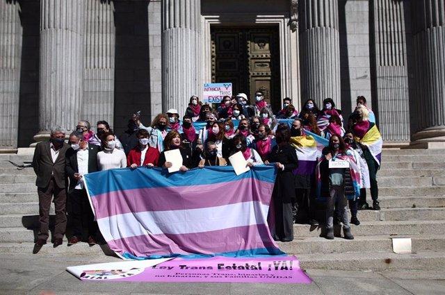 Miembros de colectivos trans posan en una fotografía tras registrar una ley en el Congreso de los Diputados
