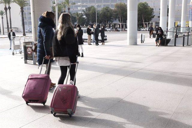 Archivo - Varias personas a las afueras del aeropuerto de Palma de Mallorca (Islas Baleares), a 20 de diciembre de 2020. A partir de este domingo, los turistas nacionales que se desplacen a Baleares procedentes de la Península deberán presentar una PCR ne
