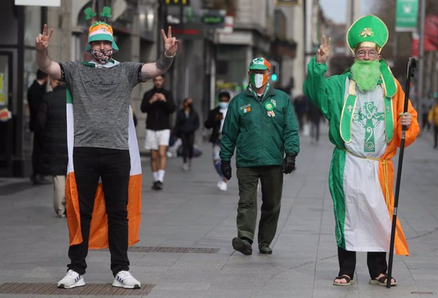 17 March 2021, Ireland, Dublin: Three men dressed up in the colours of the Irish national flag celebrate Saint Patrick's Day on O'Connell Street. Celebrations and parades for the annual St Patrick's Day event in Ireland are being held onlinefor the secon
