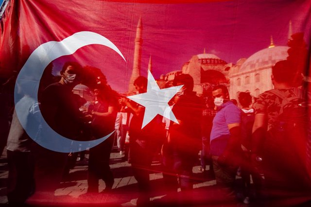Archivo - 10 July 2020, Turkey, Istanbul: People celebrate behind a Turkish national flag in front of Hagia Sophia, after a court decision to revoke the Hagia Sophia's status as a museum, paving the way for it to be turned into a mosque. Turkish President