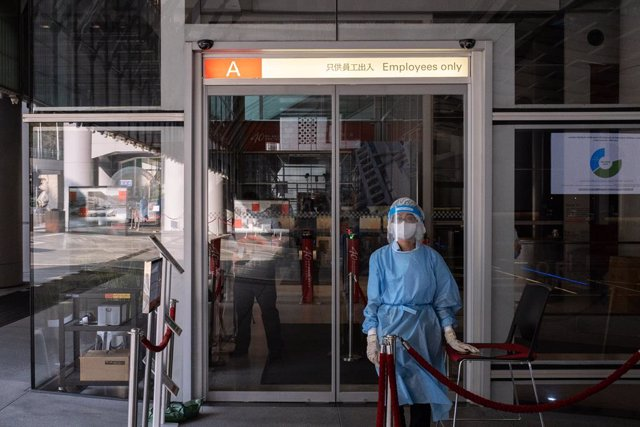 17 March 2021, China, Hong Kong: A medical worker wearing a personal protective equipment suit (PPE) stands at the main entrance of HSBC headquarters in Hong Kong. HSBC Holdings Plc's main Hong Kong office have been closed until further notice after multi