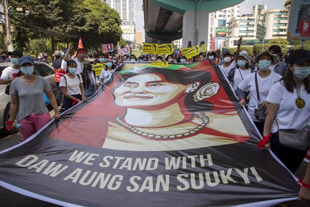 20 February 2021, Myanmar, Yangon: Protesters hold a large banner of Aung San Suu Kyi during a demonstration against the military coup and the detention of civilian leaders in Myanmar. Photo: Thuya Zaw/ZUMA Wire/dpa
