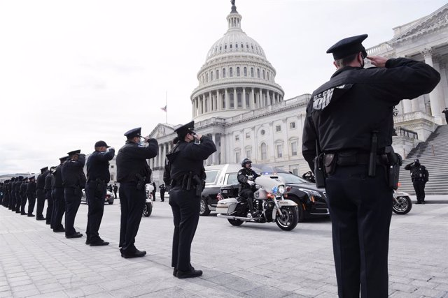 Archivo - 03 February 2021, US, Washington: US Police officers salute as the remains of Capitol Police officer Brian Sicknick is brought down after his lying in honor Congressional Tribute at USCapitol Hill. The US Capitol police officer Brian Sicknick h